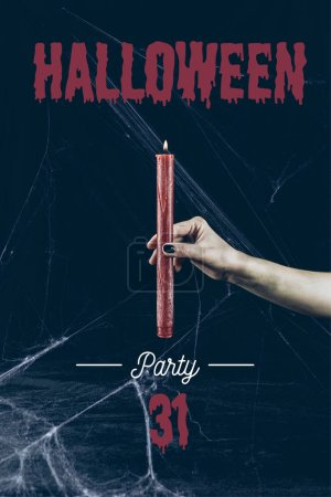 "cropped view of gothic woman holding red candle in darkness with spider web with ""halloween party 31"" lettering"