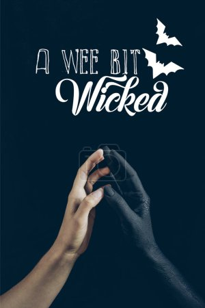 "cropped view of woman touching with black demon hand isolated on black with ""a wee bit wicked"" lettering"