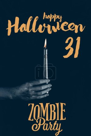 "cropped view of black hand with flaming candle, isolated on black with ""happy halloween 31 - zombie party"" lettering"