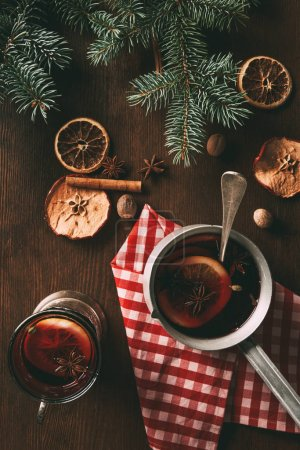 Photo for Top view of traditional christmas mulled wine with spices on wooden background with fir branches - Royalty Free Image