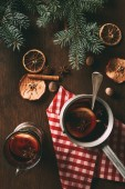 top view of traditional christmas mulled wine with spices on wooden background with fir branches
