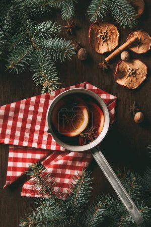 Photo for Top view of traditional christmas hot spiced wine on wooden background with dried apple slices and pine branches - Royalty Free Image