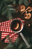 top view of traditional christmas hot spiced wine on wooden background with dried apple slices and pine branches