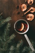 top view of traditional christmas mulled wine with spices on wooden background with pine branches