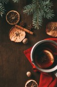 top view of traditional christmas mulled wine with dried apple slices and spices on wooden background