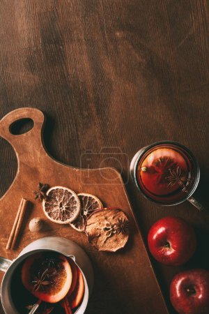 top view of homemade mulled wine with spices and apples on cutting board on wooden background