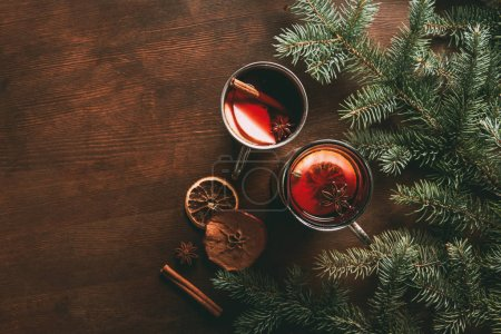 top view of glass cups with homemade hot spiced wine on wooden background with fir branches, traditional christmas drink