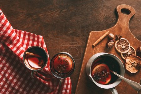 top view of glass cups with homemade mulled wine with spices on wooden background
