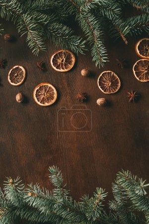 Photo pour Vue du dessus des épices de Noël sur fond en bois avec branches de sapin et espace de copie - image libre de droit