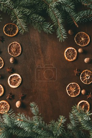 top view of frame made of dried orange slices, pine branches and spices on wooden background