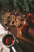 hot mulled wine in saucepan and glass cups on cutting board with dried orange slices and spices