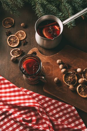 Photo for Homemade hot spiced wine in glass cup and saucepan with dried orange slices, nutmeg seeds and anise stars on wooden background - Royalty Free Image