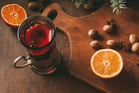 hot mulled wine with spices and orange in glass cup on wooden background
