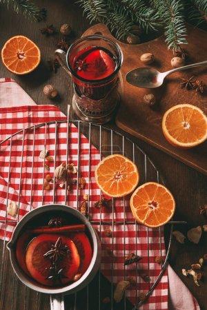 Photo pour Maison vin chaud chaud dans la tasse en verre et casserole sur une table en bois avec des épices et des oranges fraîches - image libre de droit