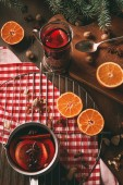 homemade hot mulled wine in glass cup and saucepan on wooden table with spices and fresh oranges