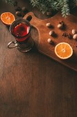 hot mulled wine with spices and orange in glass cup on wooden cutting board