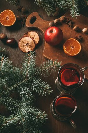 hot mulled wine in glass cups with fruits and spices on wooden background with fir branches