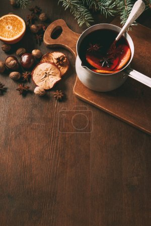 hot spiced wine in saucepan with christmas spices on wooden background