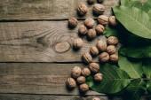 """Постер, картина, фотообои """"вид сверху натуральные грецкие орехи и зеленые листья на деревянный стол"""""""