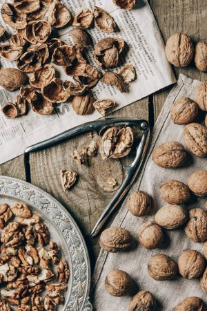 top view of whole and cracked walnuts, nutcracker, vintage plate, cloth and newspaper on wooden table