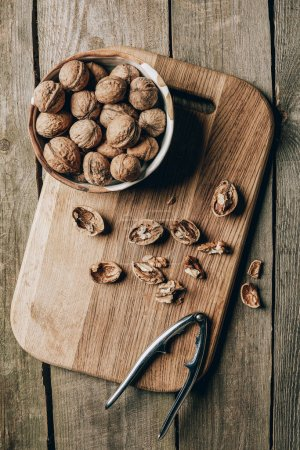 top view of walnuts in bowl and nutcracker on chopping board on wooden table
