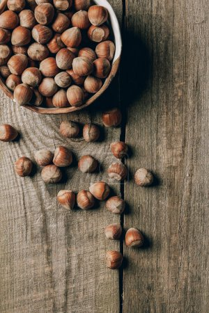 top view of tasty healthy hazelnuts in bowl on wooden table