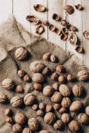 top view of hazelnuts and walnuts on sackcloth on wooden table