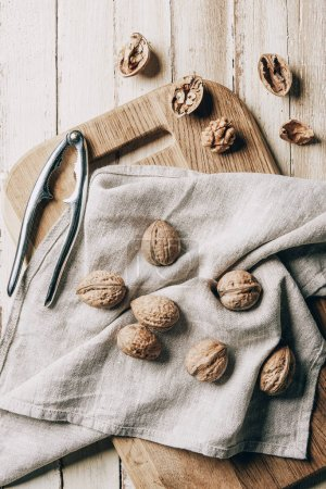 top view of walnuts on cloth, chopping board and nutcracker on wooden table