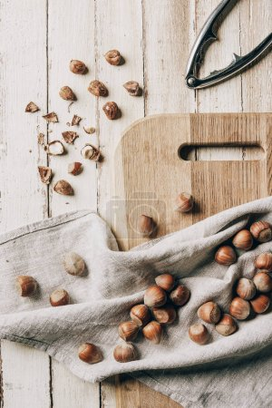top view of hazelnuts on cloth, chopping board and nutcracker on wooden table