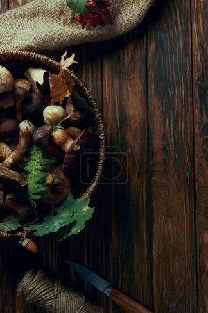top view of fresh picked edible mushrooms in basket, knife, rope and sackcloth on wooden table