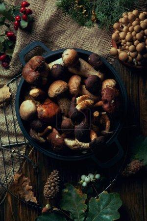 Draufsicht auf frische essbare Pilze in der Pfanne auf Holztisch