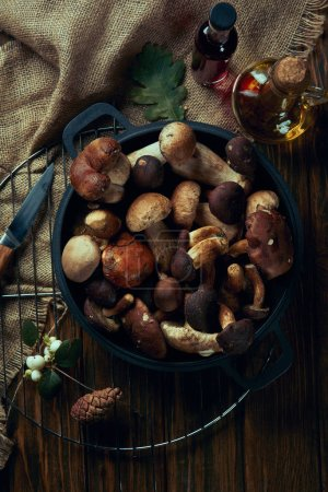 top view of fresh edible autumnal mushrooms in pan on wooden table