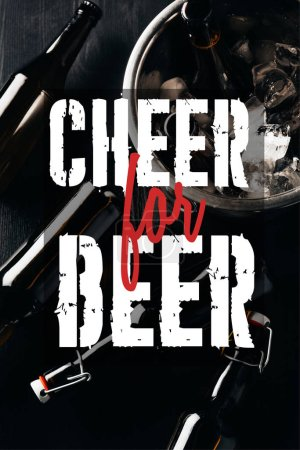"""flat lay with bucket, bottles of beer and ice cubes arranged on dark tabletop with """"cheer for beer"""" inspiration"""