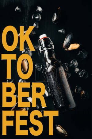 """flat lay with bottle of beer, mussels and ice cubes arranged on dark tabletop with """"oktoberfest"""" lettering"""