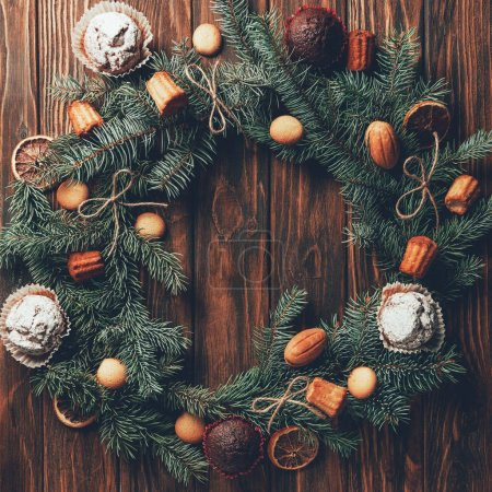 top view of fir wreath with tasty baked cookies and muffins on wooden table, christmas concept