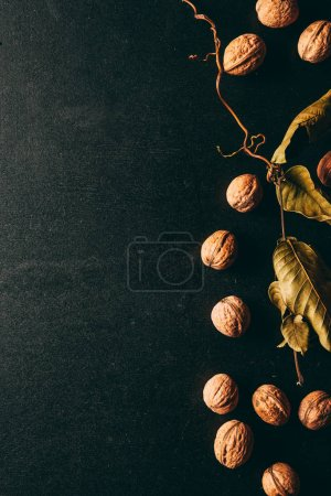 top view of chestnuts and dry leaves on black surface