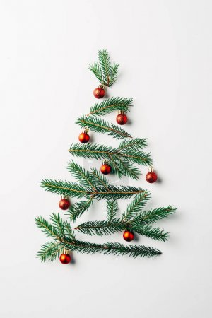 top view of pine branches arranged in christmas tree with toys on white background