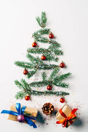 top view of green pine branch decorated as festive christmas tree with gifts and glitters on white background