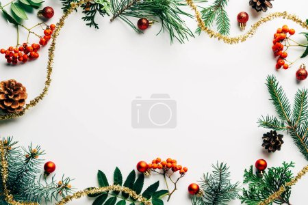 Flat lay with festive arrangement of pine tree branches, common sea buckthorn and christmas decorations on white tabletop