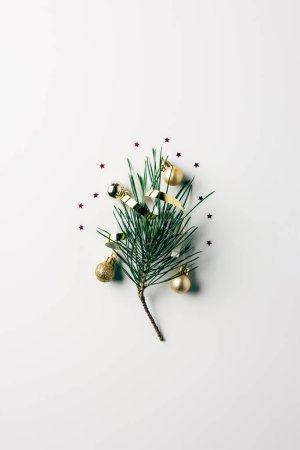 top view of little pine tree branch with ribbon and christmas toys on white surface