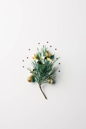 top view of little pine tree branch with ribbon and christmas balls on white surface