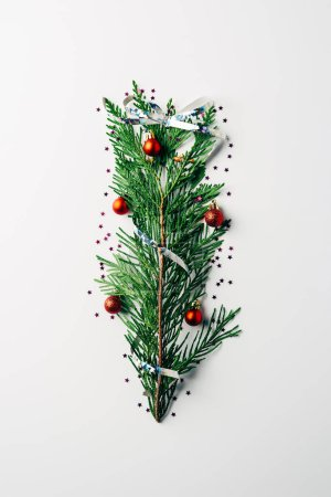 top view of green pine branch decorated as festive christmas tree on white background