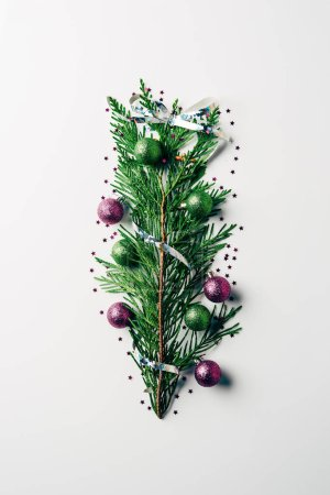 top view of green pine branch decorated with christmas toys as christmas tree on white backdrop