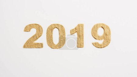 top view of 2019 year sign made of golden glitters isolated on white