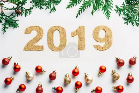 top view of 2019 year sign, pine tree branches and christmas balls on white background
