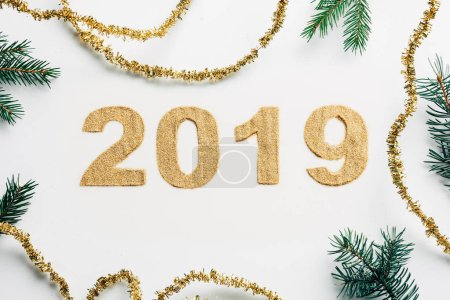 Photo for Top view of 2019 year sign made of golden glitters, garlands and pine branches on white backdrop - Royalty Free Image