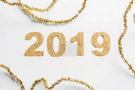 top view of 2019 year sign made of golden glitters and garlands on white backdrop