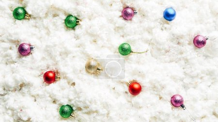 top view of colorful christmas toys on white cotton wool background