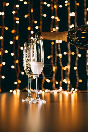 champagne pouring from bottle into glasses on garland light background, christmas concept