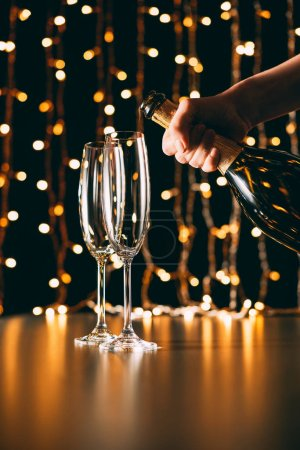 cropped image of woman holding champagne bottle near glasses on garland light background, christmas concept